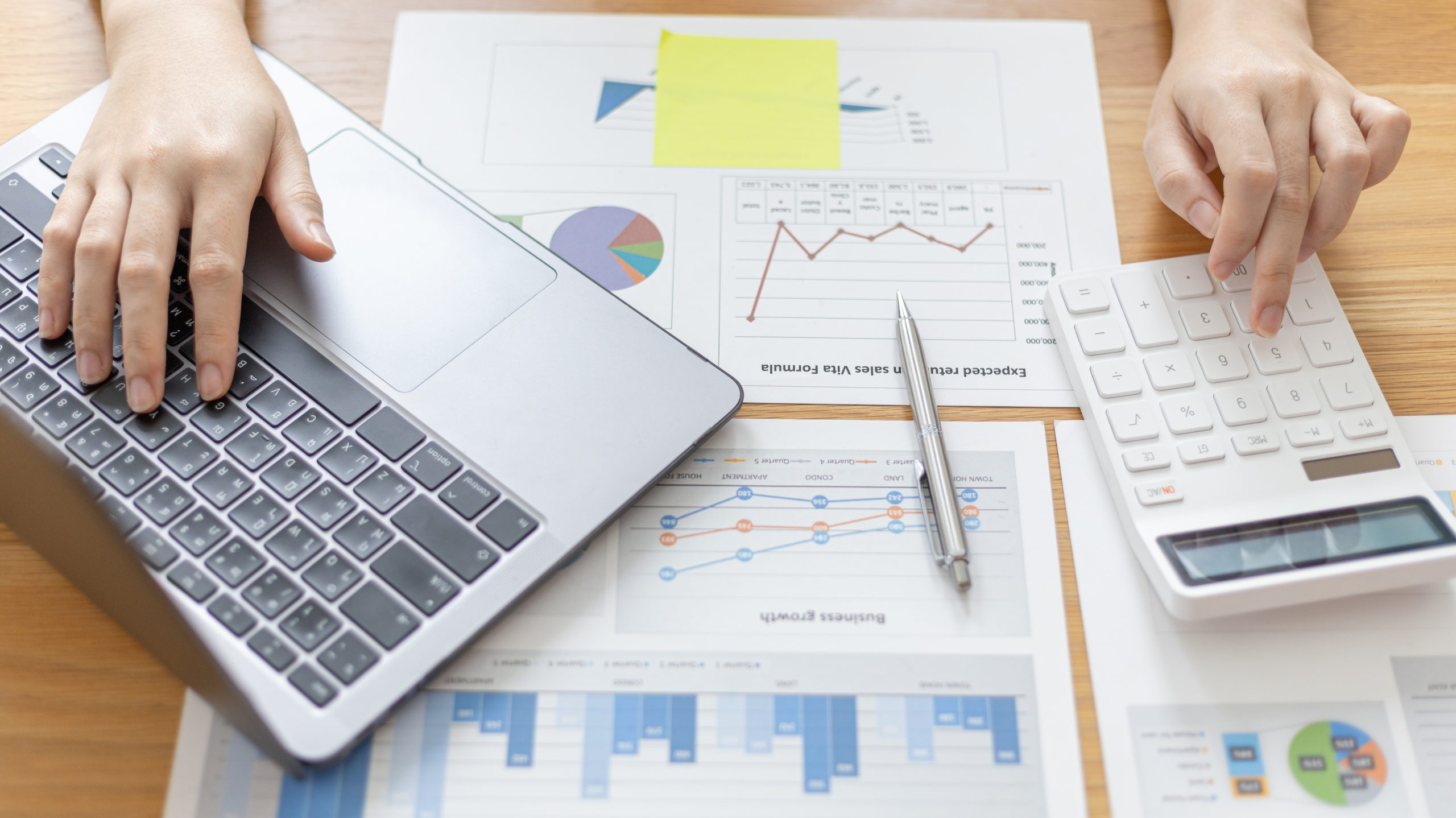 Financial businesswomen use laptop to analyze marketing strategies and real estate data to reduce company taxes for their customers, Calculate data with a calculator, Accounting and Tax concept.
